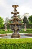 Baroque water fountain in green chateu garden Royalty Free Stock Photo