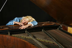 Baroque woman sleeping onon an old grand piano Stock Photos