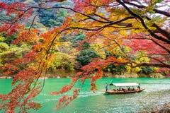 Barqueiro que punting o barco no rio Arashiyama na estação do outono ao longo do rio em Kyoto, Japão Imagens de Stock Royalty Free