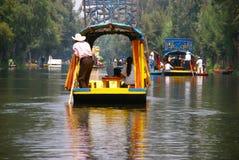 Barquero poling el barco brillantemente coloreado Fotos de archivo libres de regalías