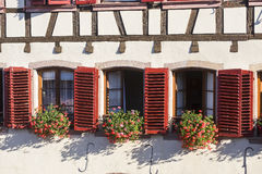 Barr (Alsace) Three windows with red shutters Stock Photography
