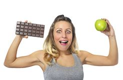 Barra attraente della mela e di cioccolato della tenuta della donna in frutta sana contro la tentazione dolce degli alimenti indu Fotografia Stock Libera da Diritti