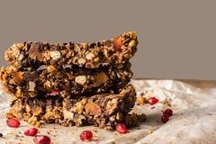 Barra casalinga sana di muesli con i cereali, il cioccolato e il pomegran Immagine Stock