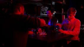 Barra con la iluminación de neón Amigos que pasan el tiempo junto Cerveza de colada en los vidrios almacen de video