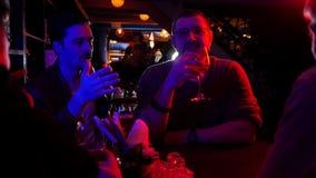 Barra con la iluminación de neón Amigos que pasan el tiempo junto que habla Un hombre en los vidrios que cuentan historia metrajes