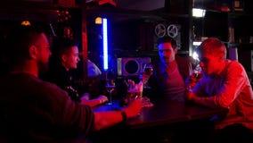 Barra con la iluminación de neón Tiempo del gasto de cuatro amigos junto almacen de metraje de vídeo