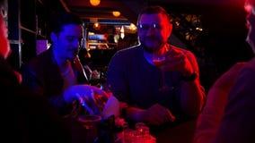 Barra con la iluminación de neón Tiempo del gasto de los amigos junta que habla y que bebe la cerveza del vidrio metrajes