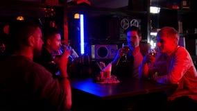 Barra con la iluminación de neón Tiempo del gasto de los amigos junto, bebiendo la cerveza aclamaciones almacen de metraje de vídeo