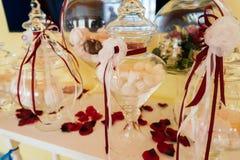Barra de caramelo del día de fiesta Céfiro en un florero de cristal adornado con las flores Fotografía de archivo
