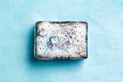 Barra de carvão de sabão preta na espuma no fundo azul fotos de stock