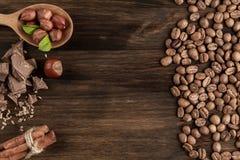 Barra de chocolate, avelã descascadas, feijões de café roasted, canela no fundo de madeira Imagem de Stock
