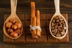 Barra de chocolate, avelã descascadas, feijões de café roasted, canela no fundo de madeira Imagem de Stock Royalty Free