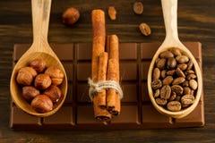 Barra de chocolate, avelã descascadas, feijões de café roasted, canela no fundo de madeira Fotos de Stock