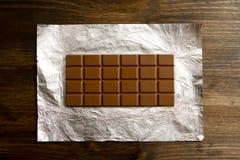 Barra de chocolate com fundo de serapilheira dos feijões da canela e de café Imagem de Stock Royalty Free