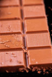 Barra de chocolate con la marca para las rebanadas sobre fondo negro Foto de archivo