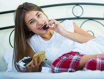 Barra de chocolate de goce morena adolescente en cama Imagenes de archivo