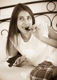 Barra de chocolate de goce morena adolescente en cama Fotos de archivo libres de regalías