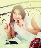 Barra de chocolate de goce morena adolescente en cama Imagen de archivo