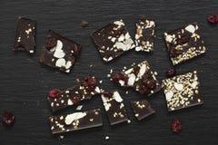 Barra de chocolate oscura con las bayas, los pistachos y la almendra en fondo negro imagen de archivo