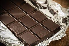 Barra de chocolate oscura en el embalaje abierto de la hoja Fotografía de archivo