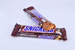 A barra de chocolate rir debochadamente em um fundo branco fotos de stock