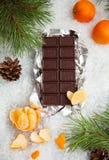Barra de chocolate saboroso com os mandarino em um fundo nevado Fotografia de Stock