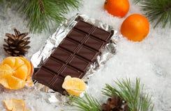 Barra de chocolate saboroso com os mandarino em um fundo nevado Fotografia de Stock Royalty Free