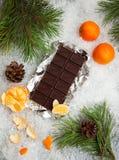 Barra de chocolate saboroso com os mandarino em um fundo nevado Imagens de Stock Royalty Free