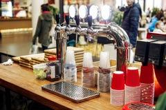Barra de la cerveza con los golpecitos elegantes y las tazas plásticas en el escritorio de madera Gato Foto de archivo