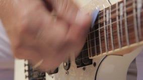 Barra de la recogida de las secuencias de una guitarra eléctrica blanca y de la guitarra del metal que son metrajes