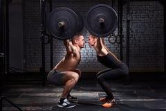 Barra de levantamento de Crossfit pela mulher e pelo homem no exercício do grupo contra a parede de tijolo fotos de stock