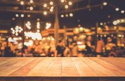 Barra de madeira do tampo da mesa com bokeh da luz do borrão no café escuro da noite imagens de stock