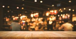 Barra de madeira do tampo da mesa com bokeh da luz do borrão no café escuro da noite imagem de stock