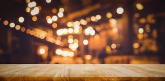 Barra de madeira do tampo da mesa com bokeh da luz do borrão no café escuro da noite foto de stock