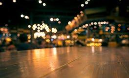 Barra de madeira vazia do tampo da mesa no restaurante do café do borrão no fundo escuro imagem de stock royalty free
