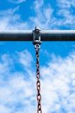 Barra de metal com a corrente oxidada que pendura contra o céu Imagem de Stock