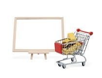 Barra de oro en carro de la compra con el tablero en blanco Imagen de archivo libre de regalías