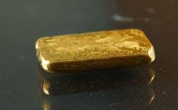 Barra de oro puesta en el fondo oscuro Imagen de archivo