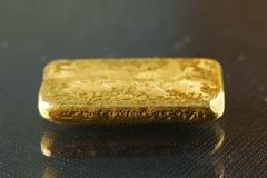 Barra de oro puesta en el fondo oscuro Fotos de archivo
