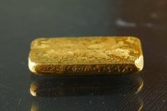 Barra de oro puesta en el fondo oscuro Fotografía de archivo libre de regalías