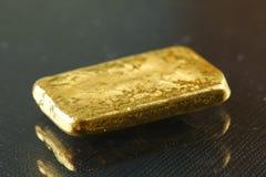 Barra de oro puesta en el fondo oscuro Imágenes de archivo libres de regalías