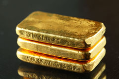 Barra de oro puesta en el fondo oscuro Foto de archivo libre de regalías