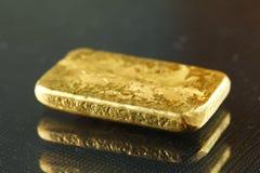 Barra de oro puesta en el fondo oscuro Imagen de archivo libre de regalías