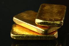 Barra de oro puesta en el fondo oscuro Fotos de archivo libres de regalías
