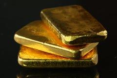 Barra de oro puesta en el fondo oscuro Foto de archivo