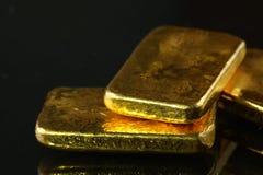 Barra de oro puesta en el fondo oscuro Imagenes de archivo