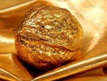 Barra de ouro com uma porca da folha de ouro em um fundo do ouro Fotografia de Stock