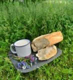 Barra de pan con leche y el manojo de flores Foto de archivo libre de regalías