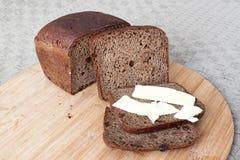 Barra de pan cortada con una mantequilla Foto de archivo