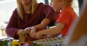 Barra de pan del corte de la madre y del hijo en la mesa de comedor 4k almacen de metraje de vídeo